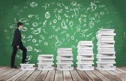 Um homem está indo acima usar-se as escadas que são feitas dos livros brancos Os ícones educacionais são tirados no quadro verde Fotos de Stock