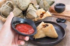 Um homem está indo comer a bolinha de massa do zongzi ou do arroz em Dragon Boat Festival fotografia de stock royalty free