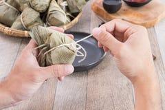 Um homem está indo comer a bolinha de massa do zongzi ou do arroz em Dragon Boat Festival foto de stock royalty free