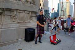 Um homem está jogando gaitas de fole na rua imagens de stock royalty free