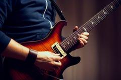 Um homem está jogando a guitarra elétrica Fotos de Stock Royalty Free