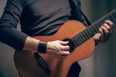 Um homem está jogando na guitarra acústica do vintage Imagem de Stock