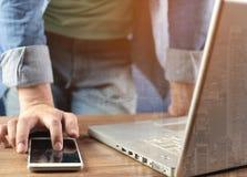 Um homem está jogando o portátil e o telefone celular com fundo da opinião da arquitetura da cidade Foto de Stock Royalty Free