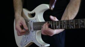 Um homem está jogando um ritmo em uma guitarra elétrica branca em um fundo preto Jogo profissional da guitarra filme