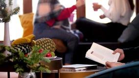 Um homem está lendo um livro Mulheres que conversam no fundo video estoque