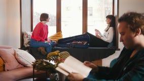 Um homem está lendo um livro Uma conversa fêmea no fundo video estoque