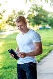 Um homem está lendo um telefone em seus fones de ouvido, com uma garrafa da proteína em sua mão Atleta muscular, sorriso feliz de Fotografia de Stock