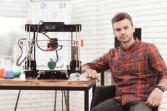 Um homem está levantando perto da impressora 3d em que apenas imprimiu um modelo da maçã É muito satisfeito com o resultado Imagem de Stock Royalty Free