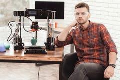 Um homem está levantando perto da impressora 3d em que apenas imprimiu um modelo da maçã É muito satisfeito com o resultado Imagens de Stock