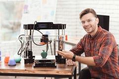 Um homem está levantando perto da impressora 3d em que apenas imprimiu um modelo da maçã É muito satisfeito com o resultado Imagens de Stock Royalty Free