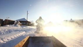 Um homem está montando um carro de neve na vila filme