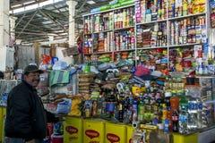 Um homem está na frente de sua tenda em um mercado em Cusco no Peru Fotografia de Stock Royalty Free