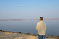 Um homem está no banco de rio e controla o zangão Foto de Stock Royalty Free