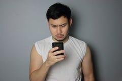 Um homem está olhando no telefone celular imagem de stock royalty free