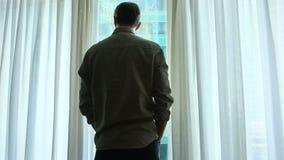Um homem está pela janela com cortinas em uma sala de hotel, olha uma paisagem surpreendente da cidade video estoque
