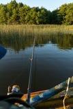 Um homem está pescando de um barco Vista atrás do ombro de um homem, você pode ver a vara de pesca e o flutuador Foto de Stock Royalty Free
