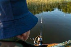 Um homem está pescando de um barco Vista atrás do ombro de um homem, você pode ver a vara de pesca e o flutuador Foto de Stock
