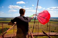 Um homem está preparando um paraquedas vermelho para o salto baixo foto de stock royalty free