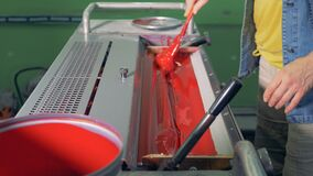 Um homem está preparando a pintura vermelha para a máquina de impressão filme