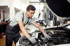 Um homem está procurando erros em um motor de automóveis foto de stock