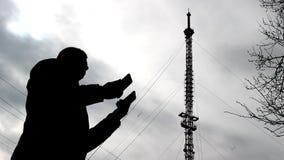Um homem está procurando uma conexão nos telefones, uma conexão má, uma torre do telefone, 3g, 4g, 5g video estoque