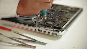 Um homem está reparando um portátil O conceito do reparo do computador Feche acima do cartão-matriz do portátil do reparo do home video estoque