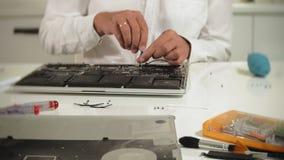 Um homem está reparando um portátil O conceito do reparo do computador Feche acima do cartão-matriz do portátil do reparo do home filme