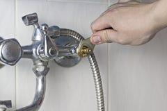 Um homem está reparando uma torneira de água, um reparo do close-up fotos de stock