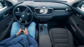Um homem está sentando-se dentro do auto que conduz carros autônomos do piloto automático vídeos de arquivo