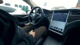 Um homem está sentando-se em um veículo que esteja sendo conduzido automaticamente video estoque