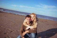 Um homem está sentando-se na areia e uma mulher está abraçando-o Imagem de Stock
