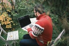 Um homem está sentando-se na rua e no trabalho Fotografia de Stock Royalty Free