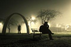 Um homem está sentando-se no banco no parque nevoento e misterioso imagem de stock