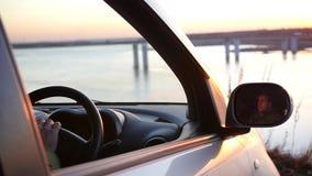 Um homem está sentando-se no carro no parque de estacionamento e está admirando-se a vista bonita e o por do sol na janela de car vídeos de arquivo