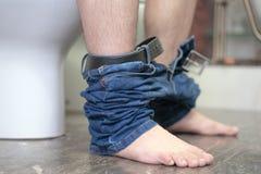Um homem está sentando-se no toalete no banheiro, com calças de brim para baixo diarrhea stomachache foto de stock royalty free