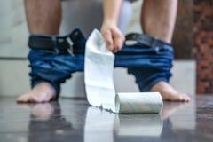 Um homem está sentando-se no toalete no banheiro, estende a mão ao papel higiênico diarrhea stomachache imagens de stock