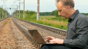 Um homem está sentando-se nos trilhos e está escrevendo-se uma letra no portátil vídeos de arquivo