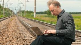 Um homem está sentando-se nos trilhos e está trabalhando-se em um portátil vídeos de arquivo