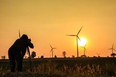 Um homem está tomando uma foto da exploração agrícola da turbina eólica fotos de stock