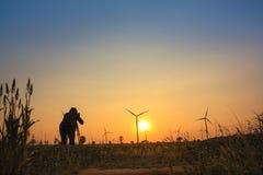 Um homem está tomando uma foto da exploração agrícola da turbina eólica imagem de stock royalty free