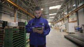 Um homem está trabalhando em uma fábrica com uma tabuleta digital, ele é vestido em um uniforme azul Operário video estoque