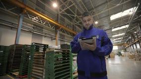 Um homem está trabalhando em uma fábrica com uma tabuleta digital, ele é vestido em um uniforme azul Operário filme