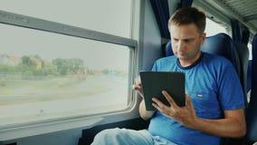 Um homem está viajando em um trem Senta-se pela janela, usa-se uma tabuleta digital Dispositivo na estrada video estoque