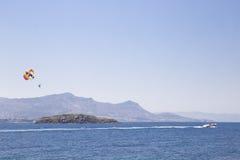 Um homem está voando em um paraglider sobre o mar, seguindo um barco t Fotografia de Stock