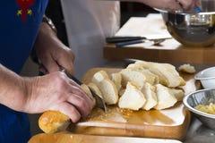 Um homem está cortando o pão Imagens de Stock Royalty Free
