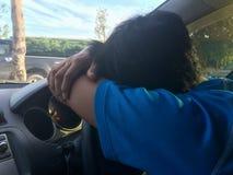 Um homem estacionado no parque de estacionamento, dormindo no carro fotografia de stock royalty free