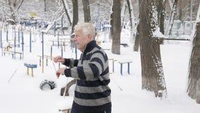 Um homem europeu idoso faz um aquecimento exterior no inverno, exercício da manhã para um aquecimento da parte traseira Vida saud vídeos de arquivo