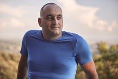 Um homem excesso de peso novo, 30-35 anos, olhando lateralmente, tiro da parte superior do corpo fotografia de stock