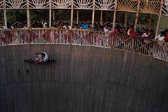 Um homem executa conluios ao montar a parede da morte em um festival que cerca NAN foto de stock royalty free