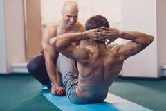 Um homem executa um exercício físico nas triturações foto de stock royalty free